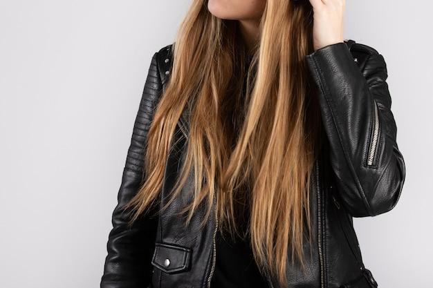 Jovem mulher vestindo uma jaqueta preta encostada em uma parede branca