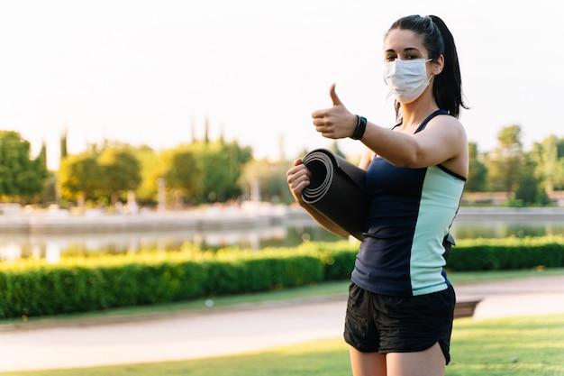 Jovem mulher vestindo uma máscara e sportswear gesticulando para ficar bem com um colchão enrolado na mão