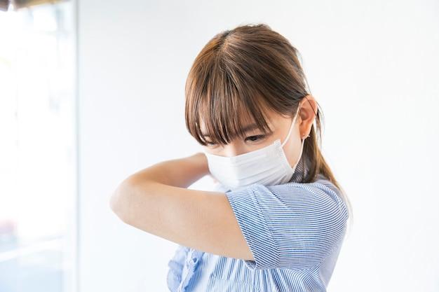 Jovem mulher vestindo uma máscara e tosse