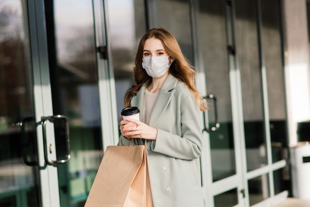 Jovem mulher vestindo uma máscara para prevenir o vírus com sacolas de compras em uma rua estreita na europa