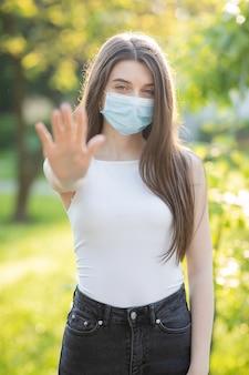 Jovem mulher vestindo uma máscara protetora no parque