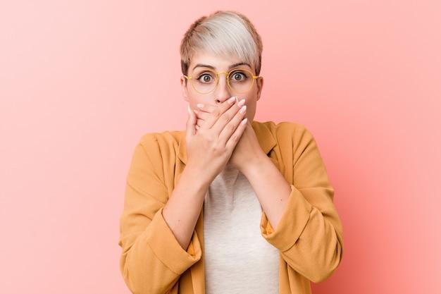 Jovem mulher vestindo uma roupa casual negócios chocou cobrindo a boca com as mãos