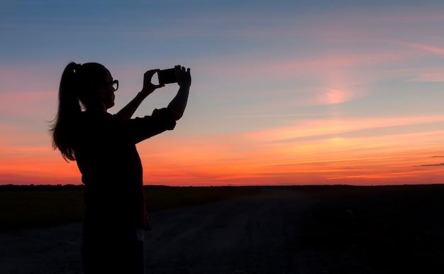 Jovem mulher viaja e tira uma foto do pôr do sol. natureza
