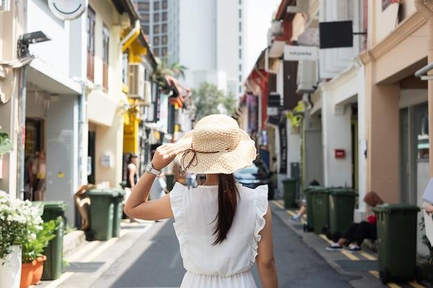 Jovem mulher viajando com vestido branco e chapéu