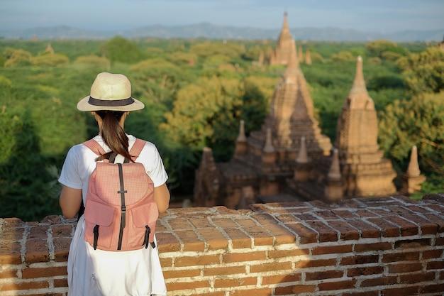 Jovem mulher viajando mochileiro com chapéu