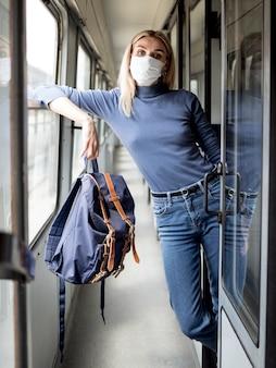 Jovem mulher viajando no trem com máscara