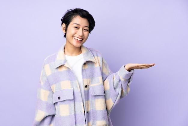 Jovem mulher vietnamita com cabelo curto ao longo da parede, segurando o espaço em branco imaginário na palma da mão