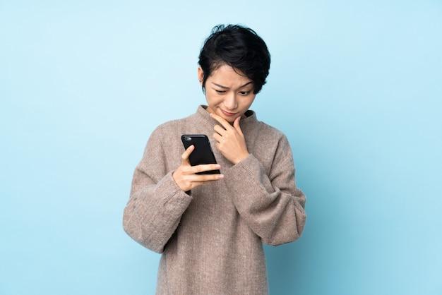 Jovem mulher vietnamita com cabelo curto na parede, pensando e enviando uma mensagem
