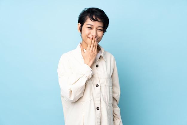 Jovem mulher vietnamita com cabelo curto sobre a boca coberta coberta com a mão