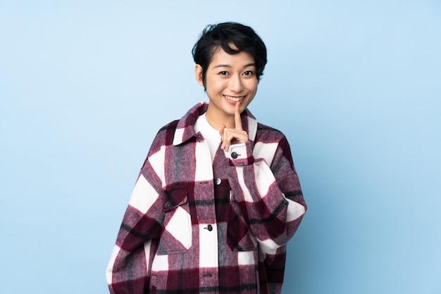 Jovem mulher vietnamita com cabelo curto sobre parede isolada, mostrando um sinal de gesto de silêncio colocando o dedo na boca