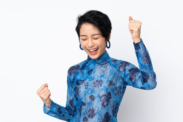Jovem mulher vietnamita com cabelo curto, vestindo um vestido tradicional sobre parede branca isolada, comemorando uma vitória