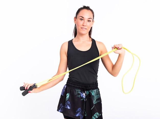Jovem mulher vista frontal com pular corda