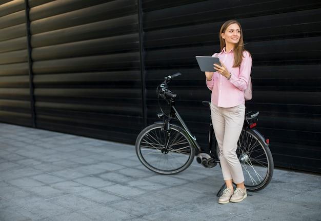 Jovem mulher witg tablet digital e bicicleta elétrica ao ar livre