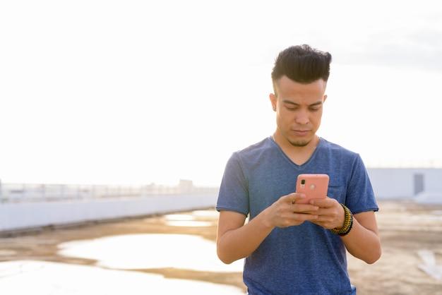 Jovem multi étnico bonito usando telefone no telhado do edifício