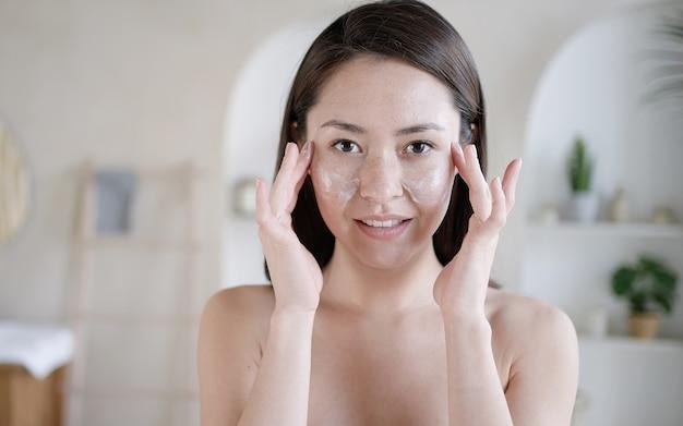 Jovem multiétnica asiática tocando o rosto com os dedos se preocupando com a pele, usa hidratante, creme, rotina matinal, higiene pessoal, cuidados com a pele, beleza, tratamentos corporais, cosméticos, conceito