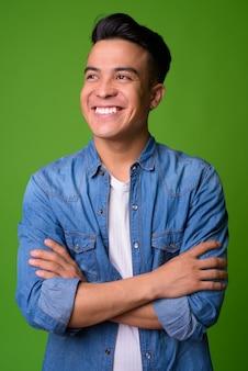 Jovem multiétnico vestindo roupas elegantes contra um fundo verde