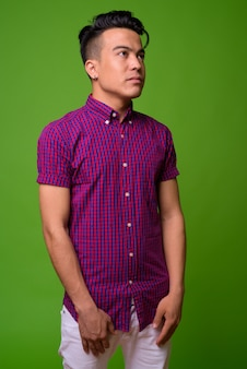 Jovem multiétnico vestindo uma camisa roxa contra um fundo verde