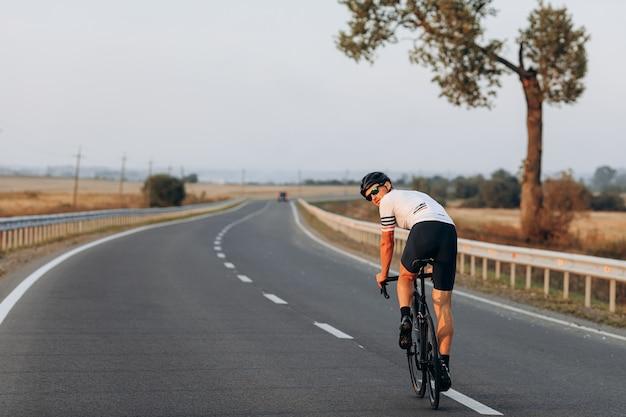 Jovem musculoso com capacete protetor e óculos andando de bicicleta preta e olhando para trás