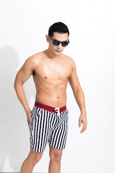 Jovem musculoso com shorts de praia listrados