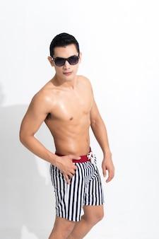 Jovem musculoso com shorts listrados tomando banho de sol e usando óculos escuros brancos