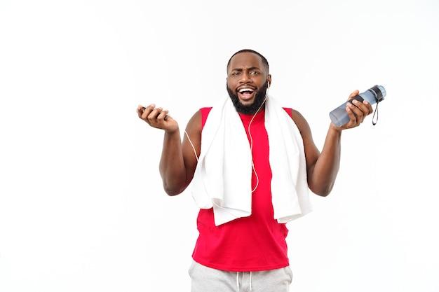 Jovem musculoso construir homem segurar garrafa de água depois de correr, atleta atraente descansando após treino ao ar livre, fitness e conceito de estilo de vida saudável. isolado no branco.