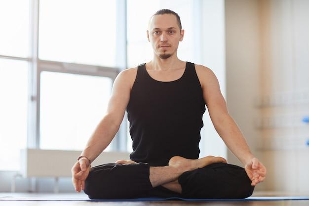 Jovem musculoso meditando sozinho