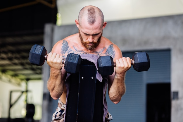 Jovem musculoso tatuado, musculoso forte barbudo, homem europeu fazendo musculação