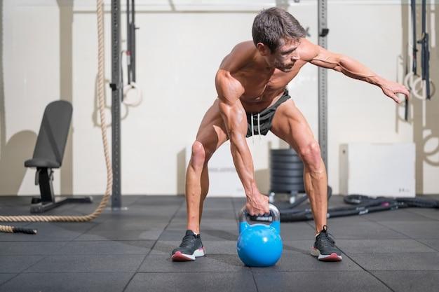 Jovem musculoso treinando com kettlebells