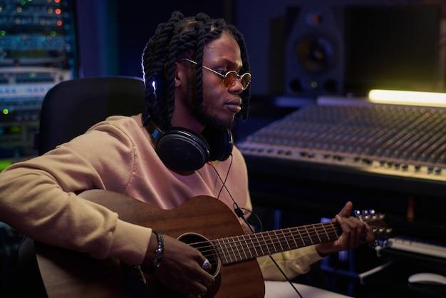 Jovem músico africano tocando violão e escrevendo uma música enquanto está sentado no estúdio de gravação