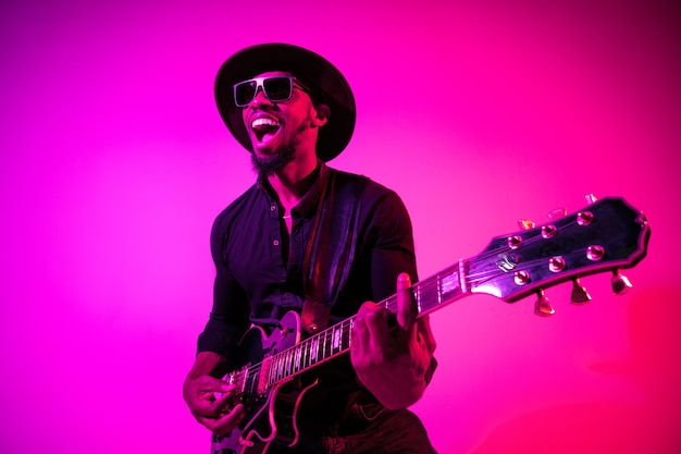 Jovem músico afro-americano tocando guitarra como uma estrela do rock em fundo gradiente rosa-púrpura em luz de néon. conceito de música, hobby. cara alegre improvisando e cantando uma música.