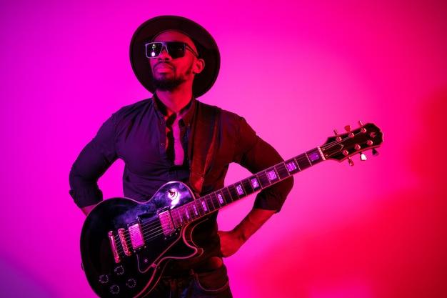 Jovem músico afro-americano tocando guitarra como uma estrela do rock em fundo gradiente rosa-púrpura em luz de néon.