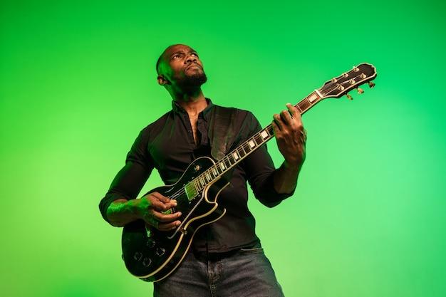 Jovem músico afro-americano tocando guitarra como uma estrela do rock em fundo gradiente verde-amarelo. conceito de música, hobby, festival, ao ar livre. cara alegre improvisando, cantando música.