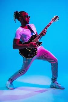 Jovem músico afro-americano tocando violão como uma estrela do rock na parede azul em luz de néon.