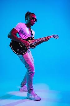 Jovem músico afro-americano tocando violão como uma estrela do rock sobre fundo azul do estúdio em luz de néon. conceito de música, hobby. cara alegre improvisando. retrato retro colorido.
