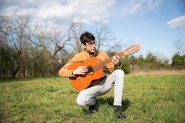 Jovem músico, ajoelhado toca violão clássico em um campo ao ar livre.