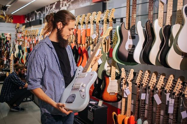 Jovem músico barbudo segura guitarra azul claro nas mãos. ele olha para isso.