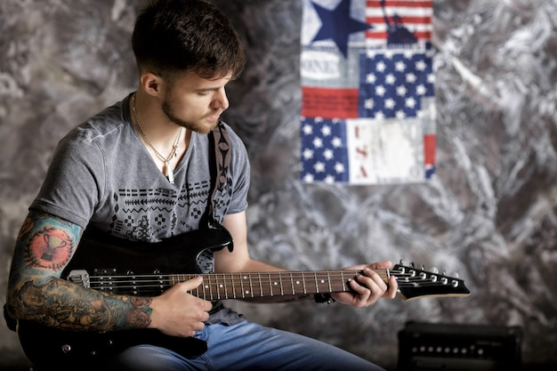 Jovem músico bonito tocando guitarra em um fundo escuro