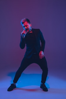 Jovem músico caucasiano, artista cantando, dançando em luz de néon em fundo gradiente