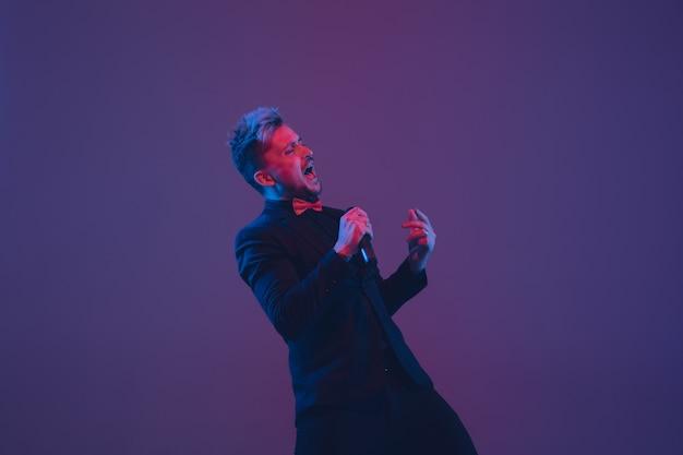 Jovem músico caucasiano cantando, dançando na luz de neon