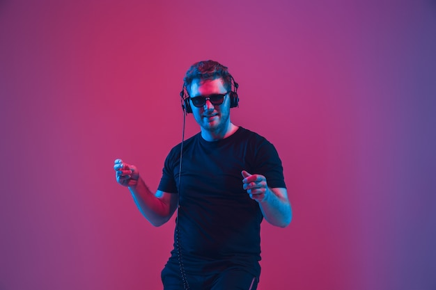 Jovem músico caucasiano em fones de ouvido cantando na parede rosa-roxa gradiente em luz de néon. conceito de música, hobby, festival. dj, anfitrião da festa alegre, fique por cima. retrato colorido do artista.