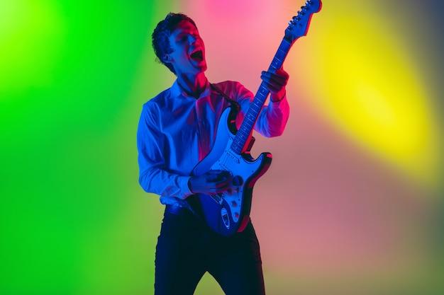 Jovem músico caucasiano, guitarrista tocando no espaço gradiente na luz de neon. conceito de música, passatempo, festival