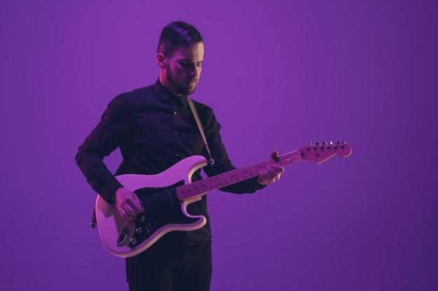 Jovem músico caucasiano tocando guitarra em luz de néon em fundo roxo