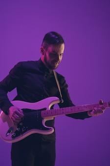 Jovem músico caucasiano tocando violão na luz de neon em roxo