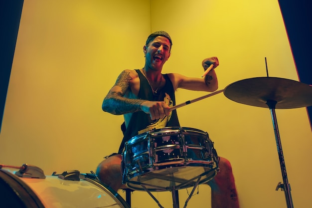 Jovem músico com bateria tocando em fundo amarelo em luz de néon. conceito de música, hobby, festival, entretenimento, emoções. baterista alegre e inspirado. retrato colorido do artista.