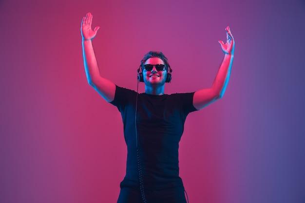 Jovem músico com fones de ouvido em luz neon