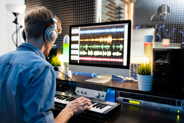 Jovem músico com fones de ouvido pressionando as teclas do teclado de piano enquanto está sentado ao lado do monitor do computador e trabalhando com sons