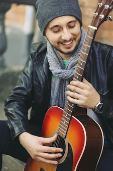 Jovem músico com guitarra na cidade