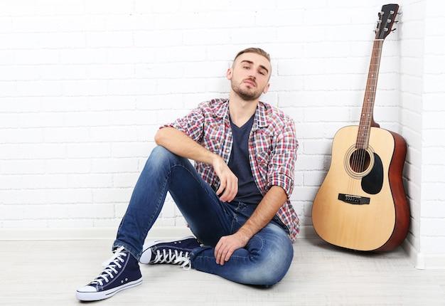 Jovem músico com guitarra na parede de luz