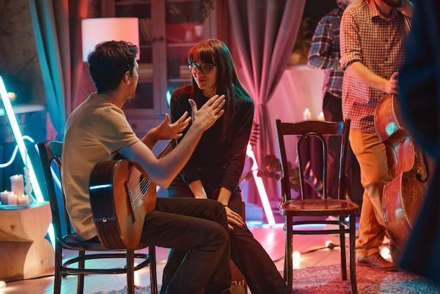 Jovem músico com guitarra sentado na cadeira e conversando com uma jovem durante o intervalo do concerto