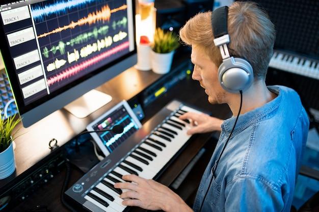 Jovem músico contemporâneo usando fones de ouvido, gravando novas músicas e canções enquanto toca no teclado do piano no estúdio
